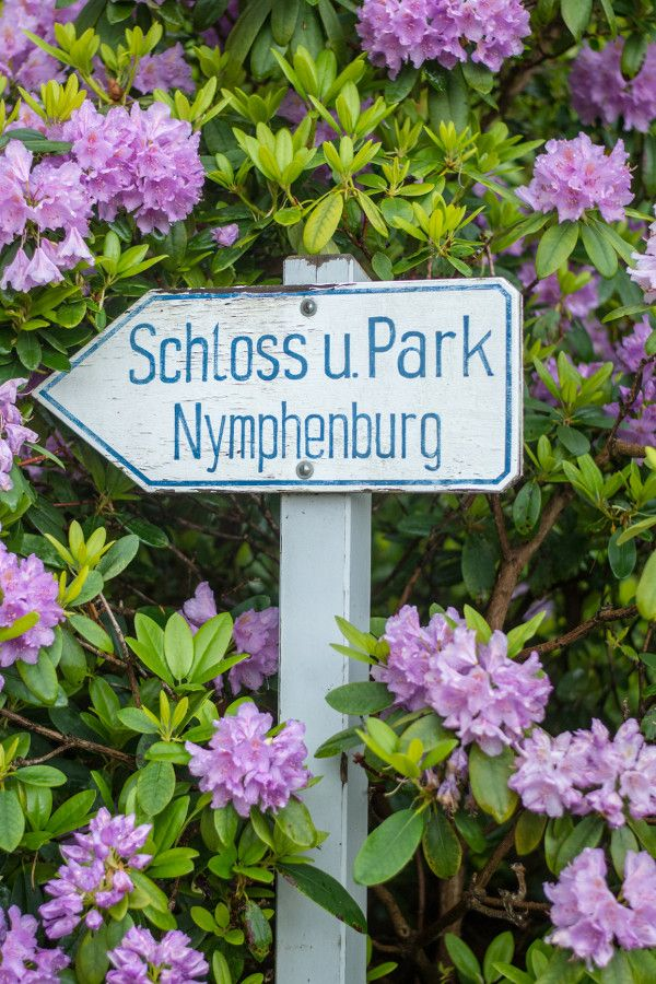 A sign pointing to Nymphenburg Palace and Park at Munich Botanical Garden in Germany.