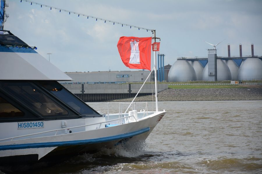 Cruise ship with Hamburg flag on the Elbe River in Germany.