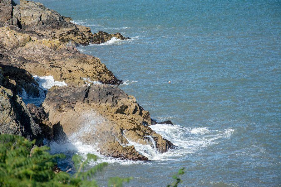 Waves crash against rocks along the coast of Howth, Ireland.