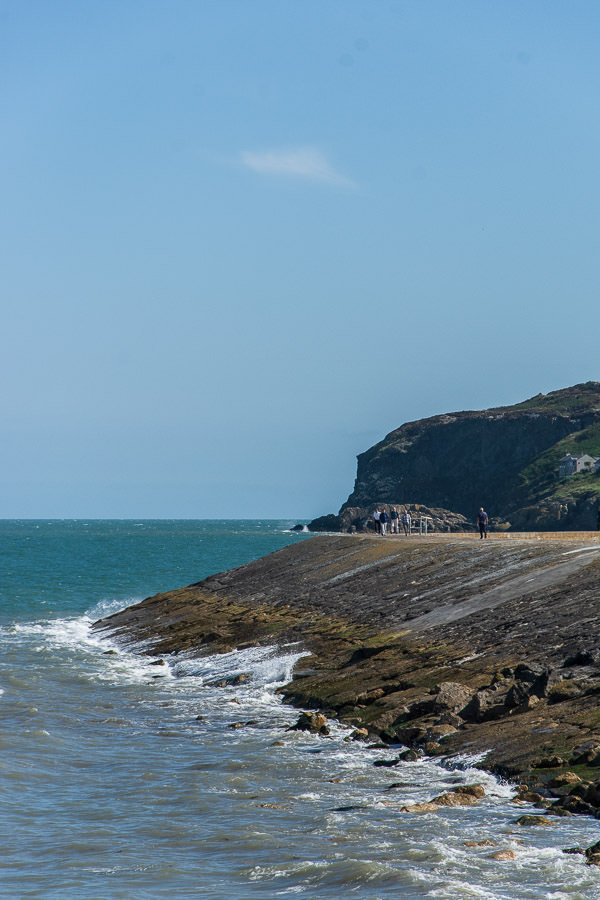 The bay rushes up on the edge of the Howth Pier .