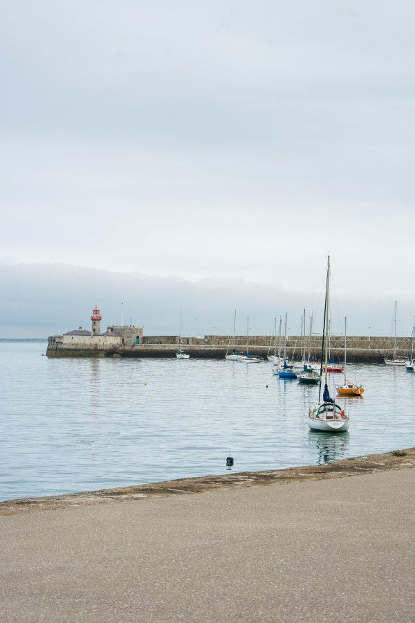 Lighthouses and sailboats in the harbor in Dún Laoghaire, Ireland.