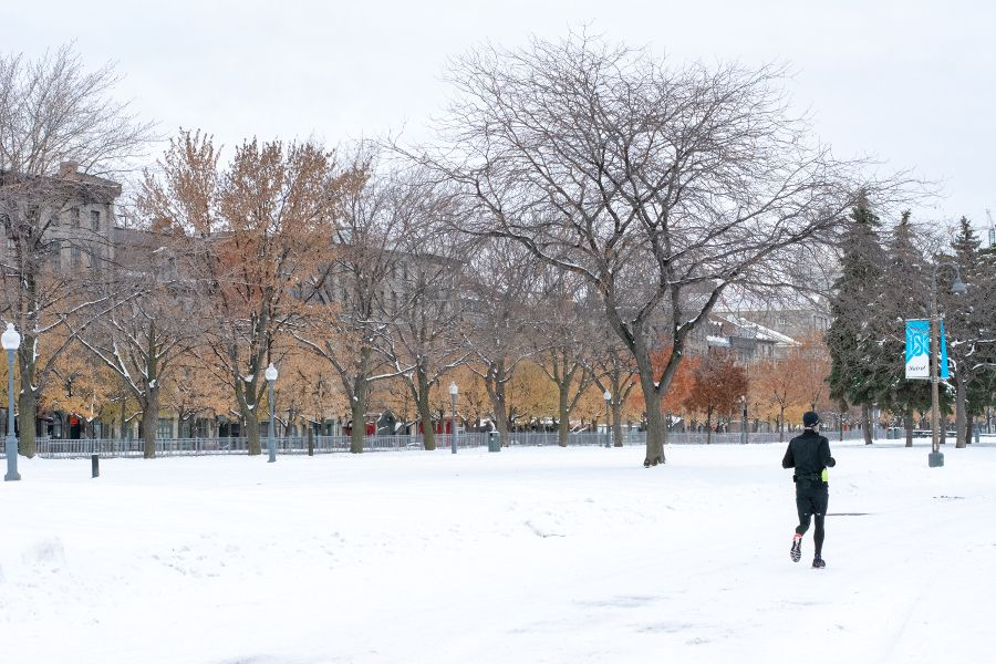 A jogger goes through the snow at Parc Lineaire de la Commune in Port Montreal with historic Old Montreal in the background.