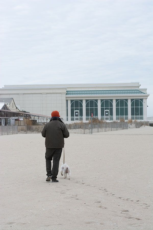 Dog and man walking towards the Cape May Convention Hall. The beaches are the best part of a Cape May dog-friendly vacation.