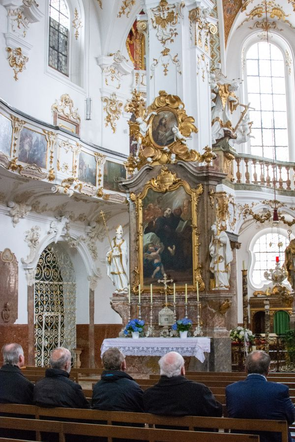 Men sit in prayer in Kloster Andech's church.