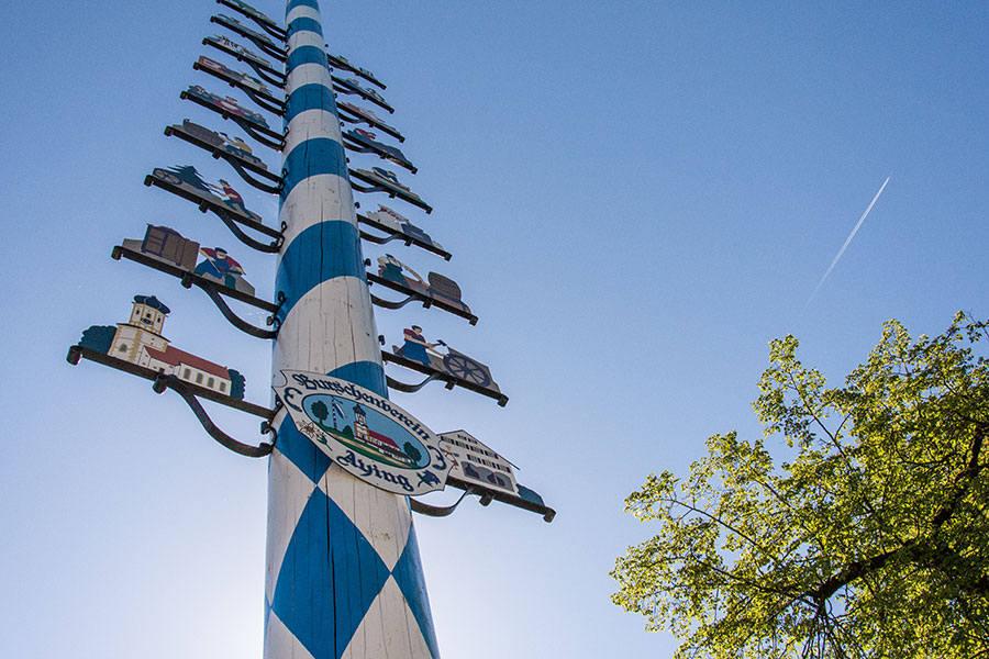 Painted white and blue for Bavaria and with signs depicting the town's businesses and trades, the Maypole (or Maibaum) stands proudly at the center of the German town of Aying.