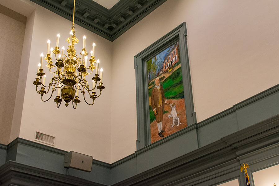 A painting and chandelier sit above a chamber of the Delaware Legislative Hall.