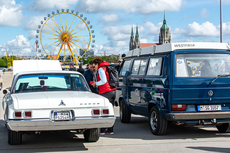 A Dodge and a VW Westfalia on show at the ACM Oldtimer-Treffen with the Munich Frühlingsfest Ferris wheel in the background.