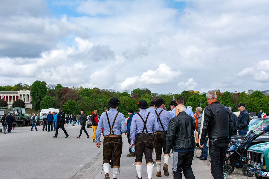 A group of men in bowler hats and Lederhosen stroll across the Wiesn.