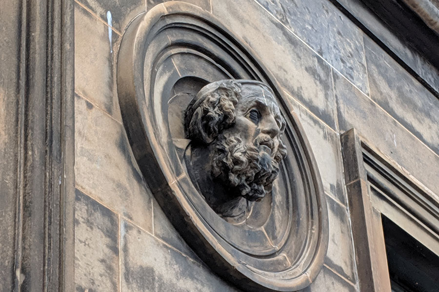 A stone head peeks out of an architectural detail on a building in Glasgow.