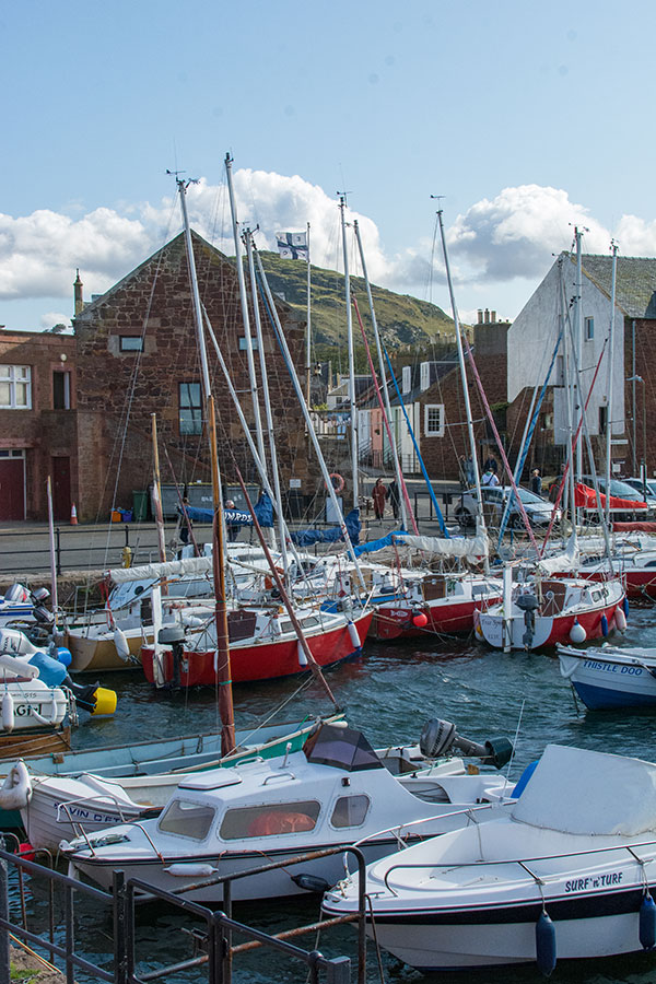 Sailboats float in the harbor at the North Berwick Yacht Club with North Berwick Law in the background.