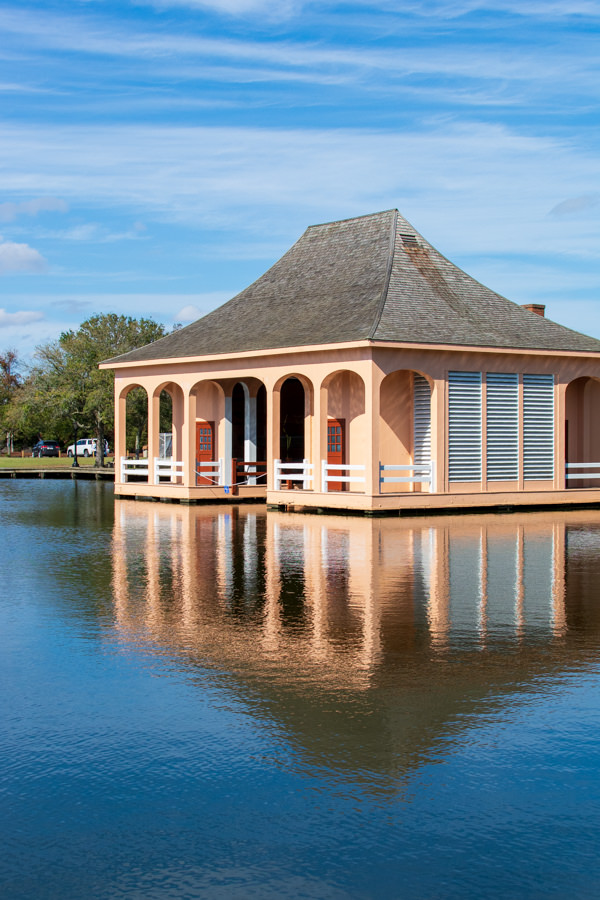A coral-colored boathouse sits on the edge of the waterfront.