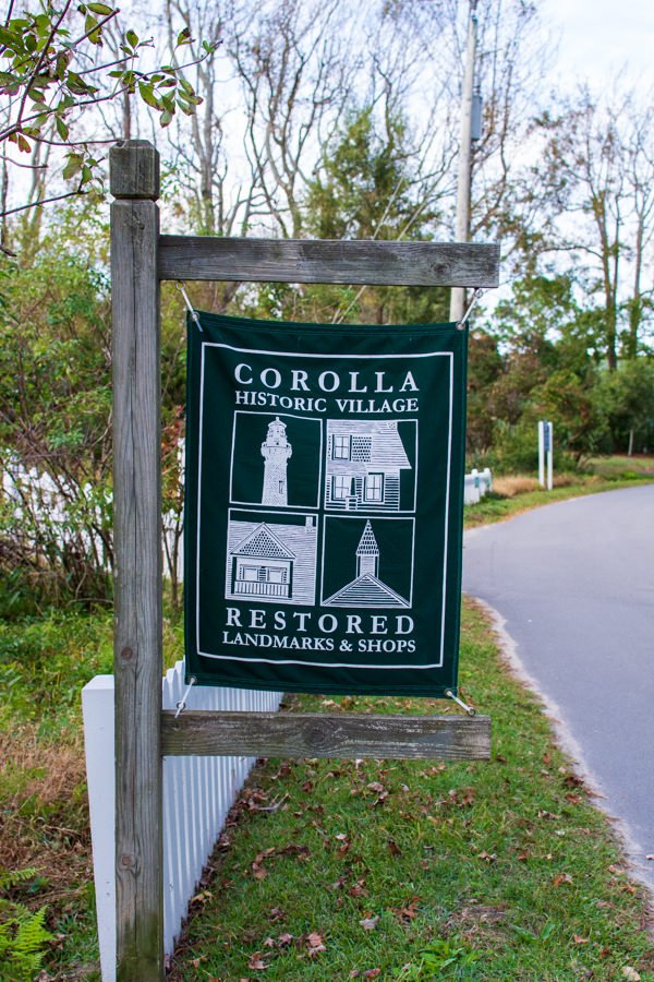 A green banner marks Historic Corolla Village, restored landmarks and shops.