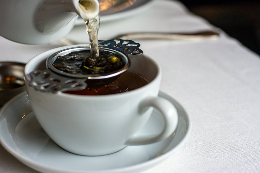 Pouring loose leaf tea into a strainer and cup at Hotel DuPont afternoon tea.