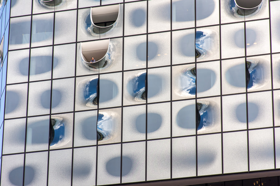 A guest leans out a window of the Elbphilharmonie.