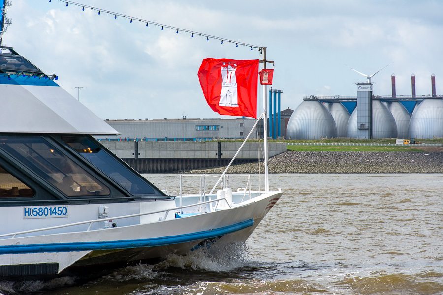 A ship flying a Hamburg flag cruises up the river.