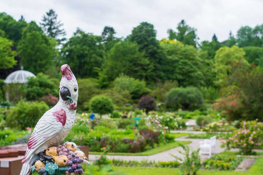 A parrot figurine by Nymphenburg Porcelain sits overlooking a garden.