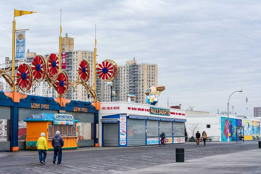 Visitors walk the boardwalk during winter at Coney Island.