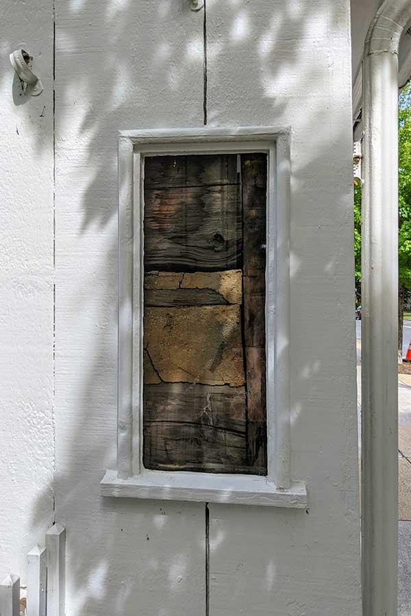A window offers a peek at the historic wood building.