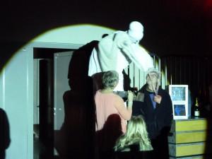 Eine Überraschung für den scheidenden Kulturamtsleiter: Der Stelzenvogel schickt Herbert Hermes mit Konfetti in den Unruhestand. (unscharfes Foto: Bernd Berke)
