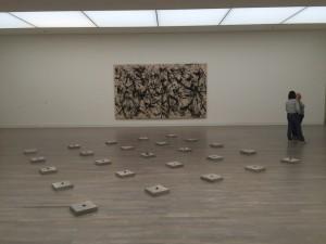 """Die Kunstsammlung, neu gemischt: """"25 Blocks and Stones"""" von Carl André aus der Sammlung Fischer vor Jackson Pollocks monumentalem Bild """"Number 32"""" von 1950. (© Kunstsammlung NRW / Foto: Birgit Kölgen)"""