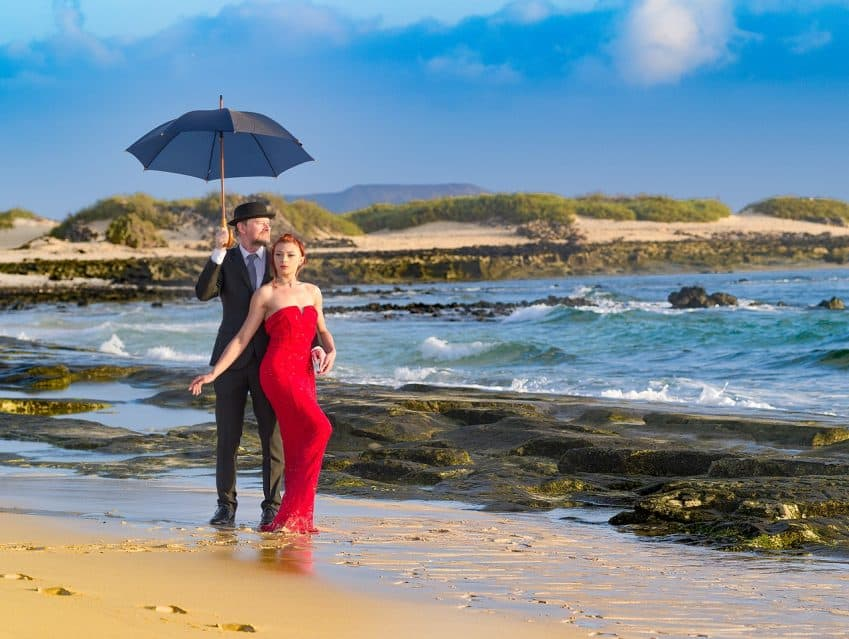 Imagem mostra homem com um terno preto, chapéu, segurando um guarda-chuva em uma praia acompanhado de uma mulher com vestido e batom vermelhos.