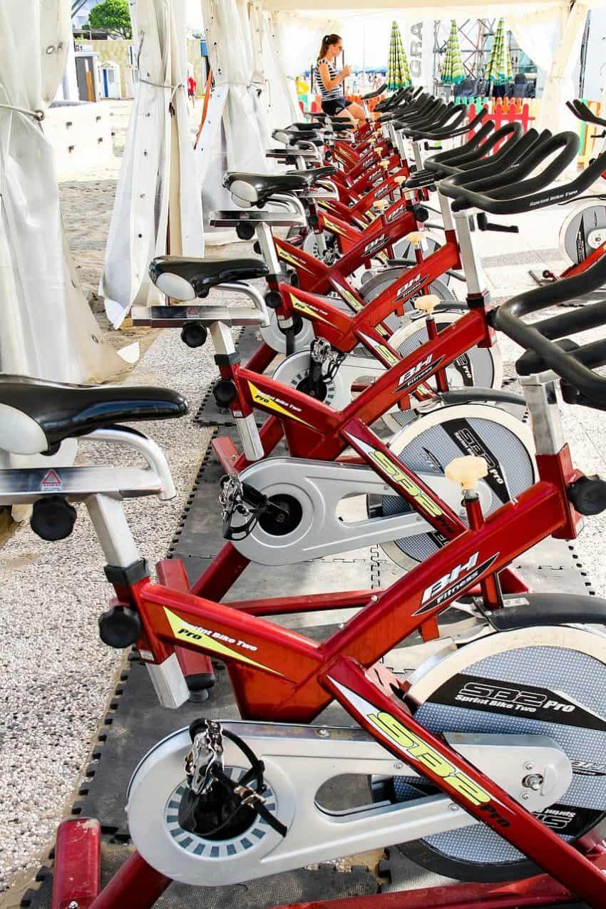 Imagem mostra fileira com 8 bicicletas ergométricas em uma academia. Ao fundo uma mulher pedala na última bicicleta da fila.