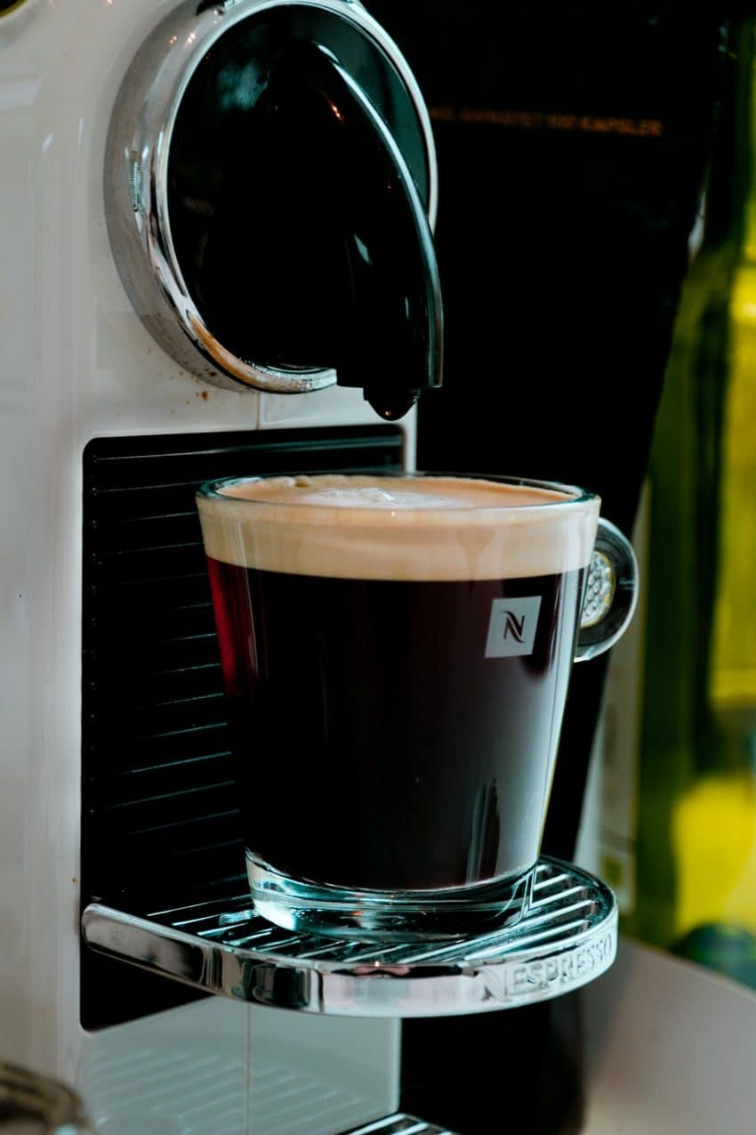 Image shows white nespresso coffee maker with coffee cup.