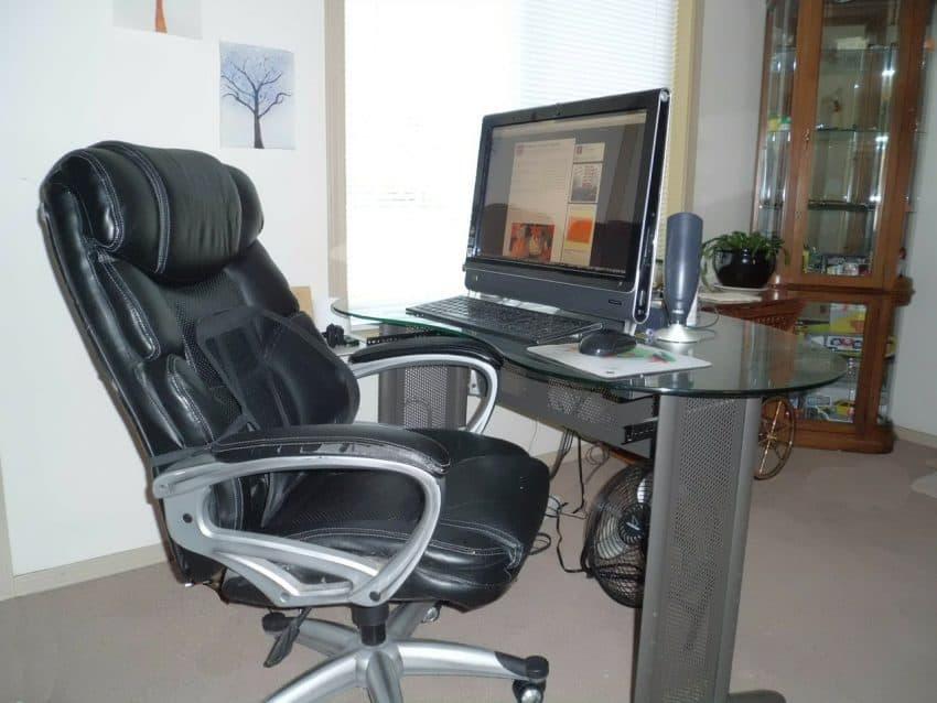 Imagem mostra cadeira de escritório preta perto do computador no home office.