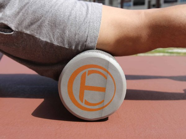 Imagem mostra homem com pernas esticadas praticando alongamento sobre rolo de massagem cilíndrico no solo.