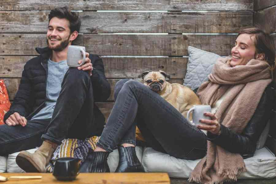 man and woman drinking coffee sitting smiling next to a dog