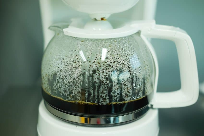 closeup of the glass jar of a white electric coffee maker with coffee