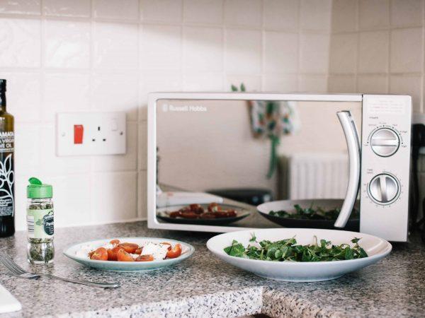 Imagem mostra alguns pratos de comida em frente a um forno de micro-ondas.