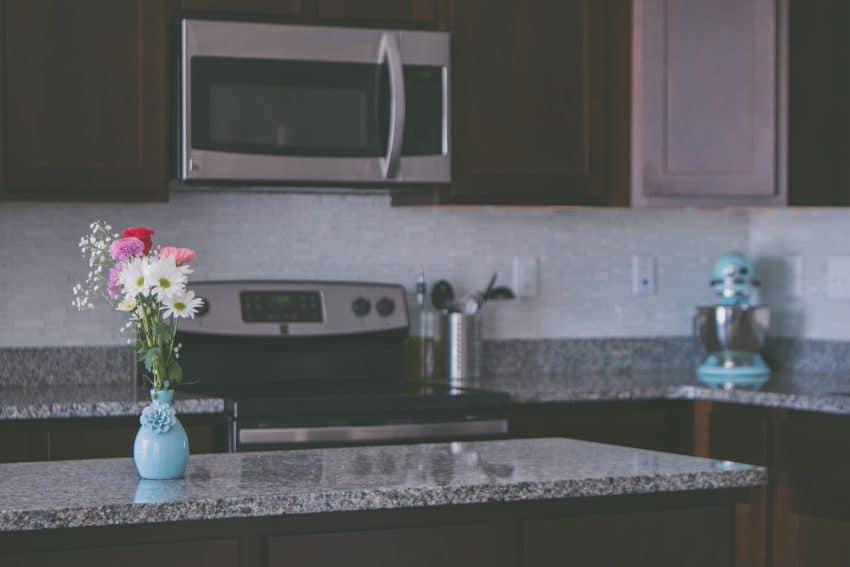 Imagem mostra um micro-ondas embutido em um móvel em cima do fogão.
