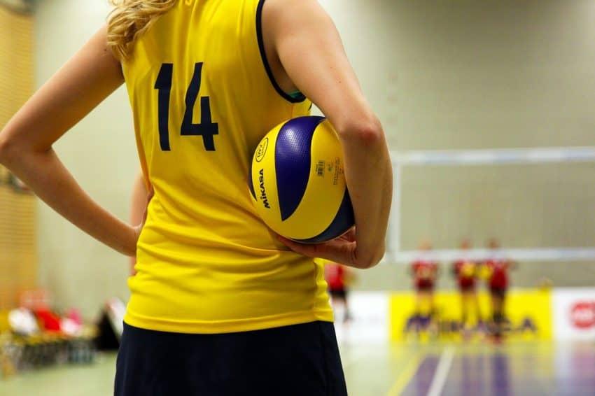 Imagem mostra jogadora com bola de vôlei na mão, de costas, vestindo uma camisa número 14, amarela.