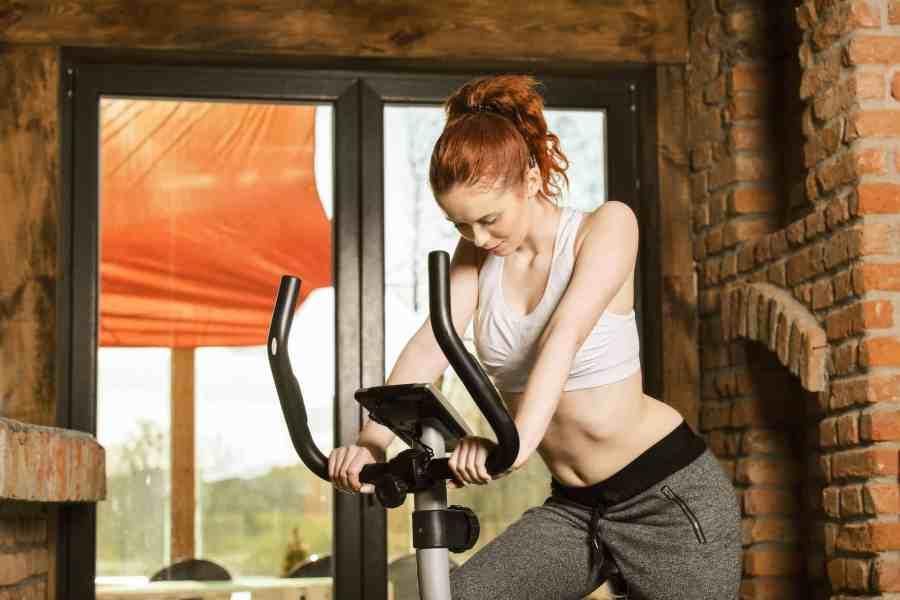 Mulher fazendo exercício com bicicleta ergométrica.