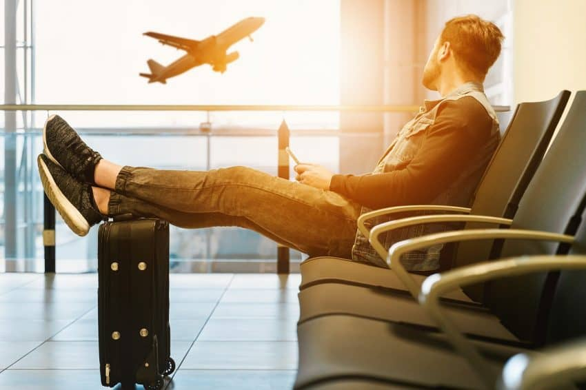 Homem sentado em aeroporto com os pés em cima da mala.