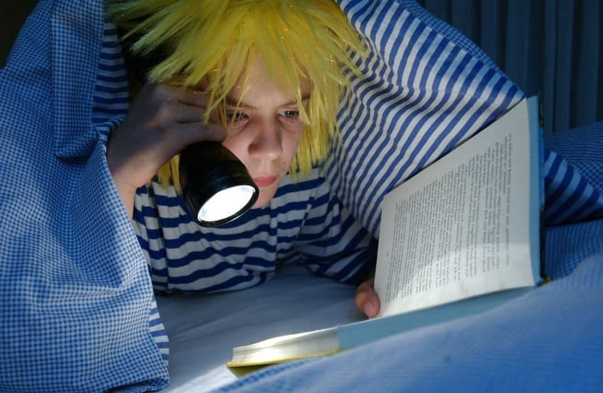 Menino lendo livro na cama à noite usando uma lanterna.