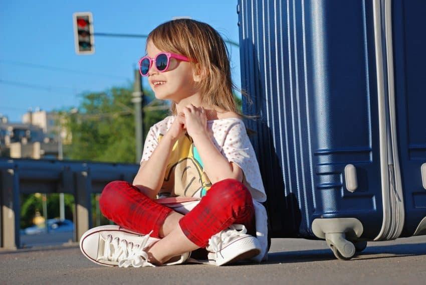 Menina feliz sentada ao lado da mala de viagem.