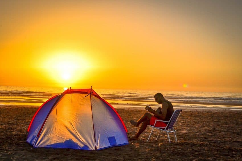 Imagem mostra uma barraca na areia da praia e um homem sentado ao lado, em uma cadeira, tocando violão.