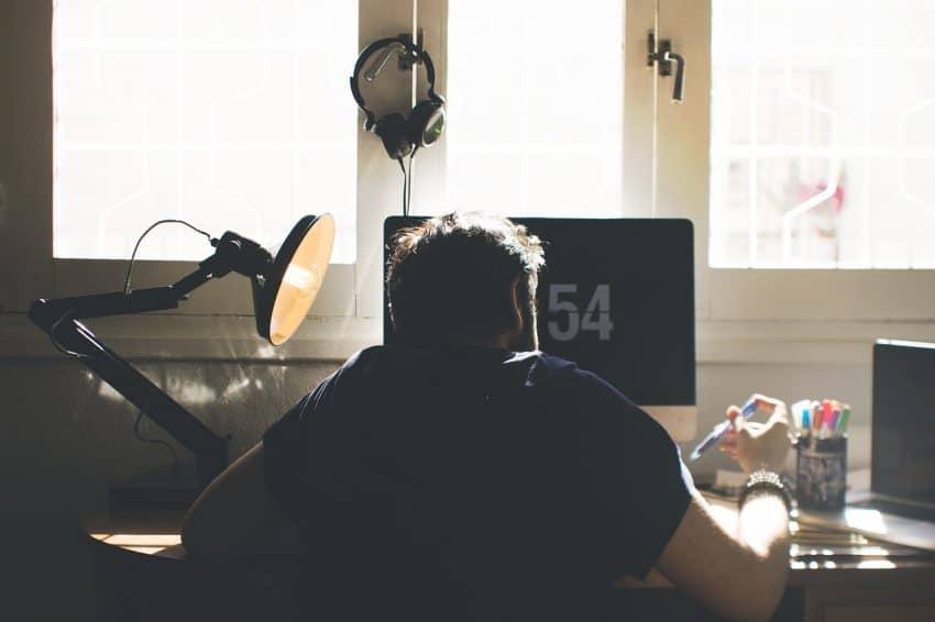 Imagem mostra um homem de costas para a câmera, em frente à uma tela de computador. Ele anota algo com uma caneta, iluminado por uma luminária de luz direta no seu lado esquerdo.