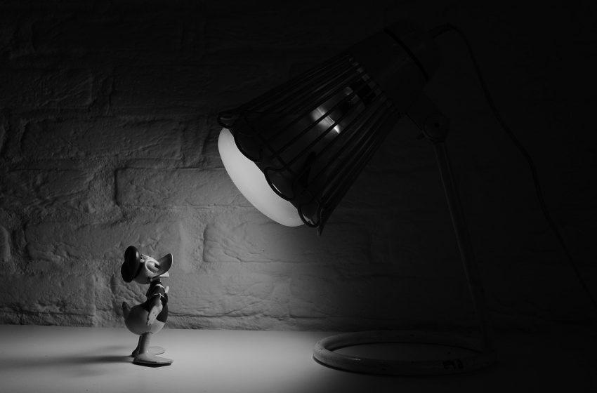 Imagem mostra uma luminária de luz direta, mas de design arrojado, iluminando um pequeno boneco do Pato Donald.