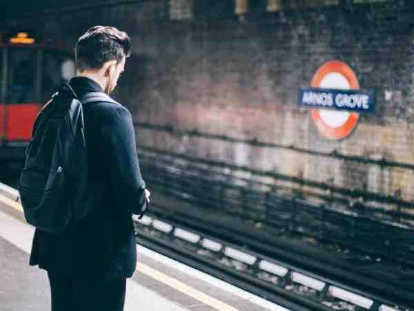 Homem com mochila preta nas costas na estação de metrô.