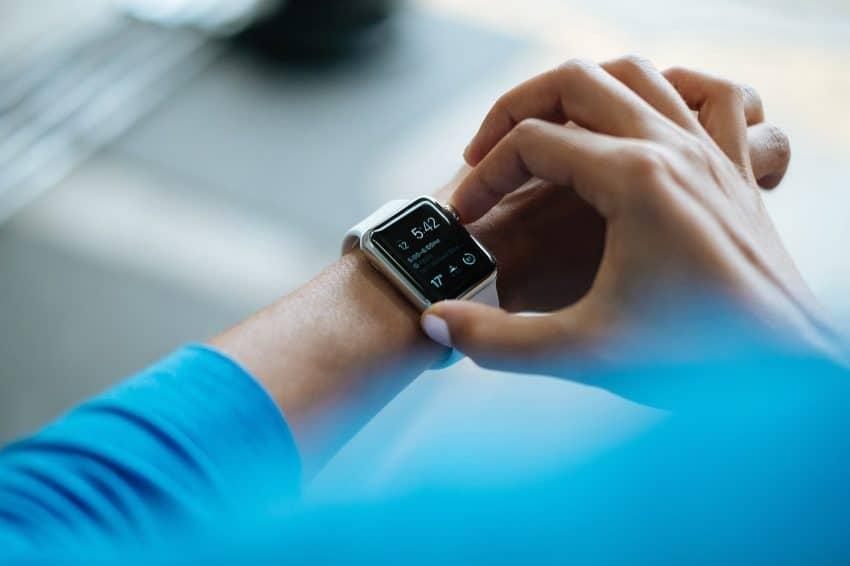 Woman using white Apple smartwatch.