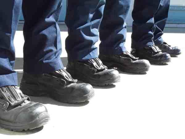 Destaque dos pés de três homens em fileira, com sapatos de segurança.