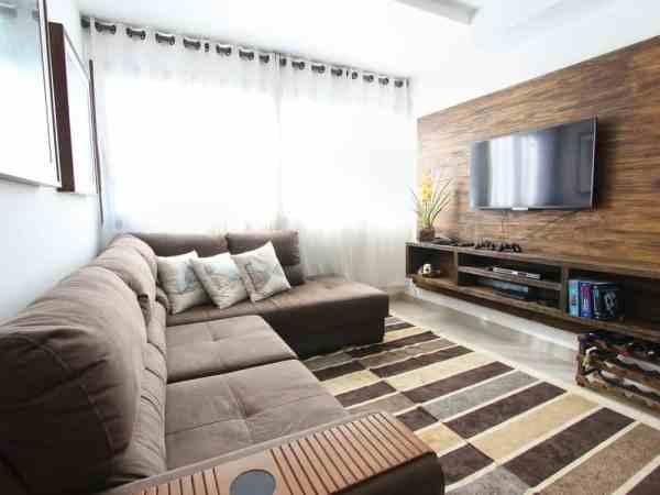 Sala de uma casa. Aparelho de televisão na parede.