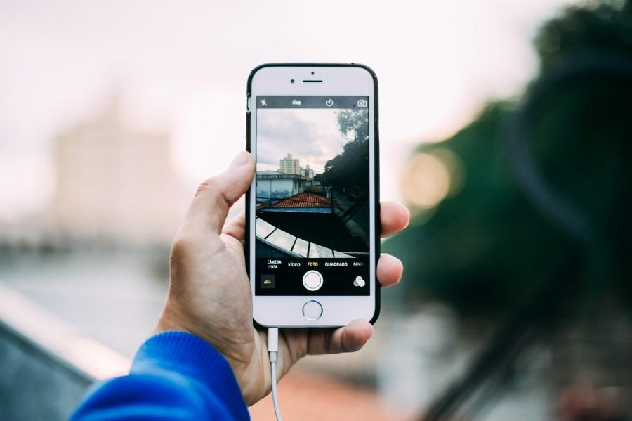 Imagem mostra uma pessoa tirando uma foto com seu smartphone.