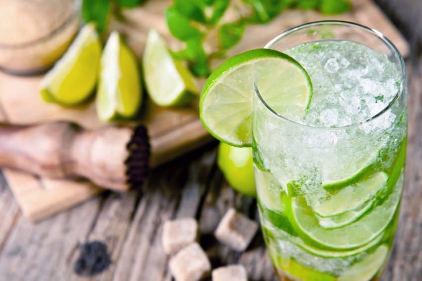 Imagem de copo com gelo triturado, bebida e limão.