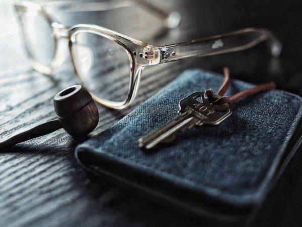 Na foto está uma carteira jeans com um par de óculos e um cachimbo ao lado e em cima uma chave.
