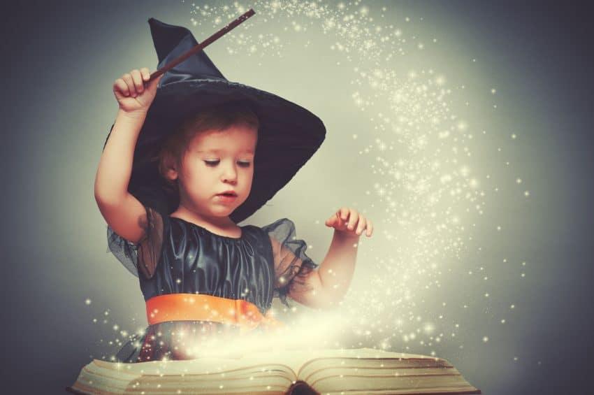 Imagem de criança fantasiada de bruxa fazendo magia com varinha e livro.
