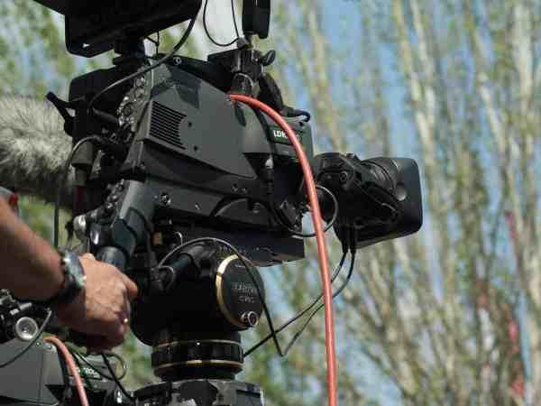 Imagem mostra uma câmera de filmagem sendo manuseada.